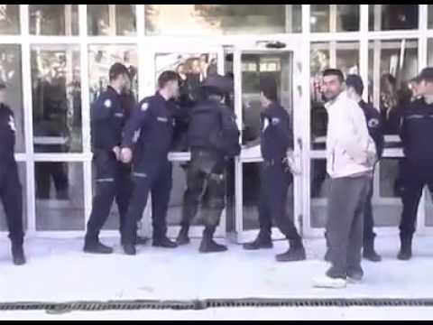 Polisman försöker sparka in en (öppen) dörr